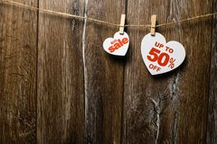 Hearts and discounts with romantic pattern on wooden background. Big sale on one heart and fifty percent. On another hanging on rope by clothespins stock photos