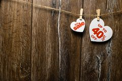 Hearts and discounts with romantic pattern on wooden background. Big sale on one heart and forty percent. On another hanging on rope by clothespins stock photos