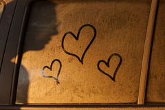 Hearts draw on water of window of a car with shadow of woman Stock Images