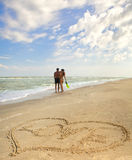 Hearts drawn on the sand. Of a beach (foreground), the man and woman on the background Royalty Free Stock Photo