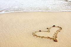 Hearts drawn in the sand with seafoam and wave Stock Photo