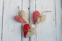 Hearts of fabric on a white table. Three handmade heart of fabric on a white table Royalty Free Stock Photo