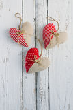 Hearts of fabric on a white table. Three handmade heart of fabric on a white table Stock Photo