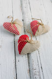 Hearts of fabric on a white table. Three handmade heart of fabric on a white table Royalty Free Stock Photos