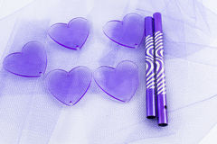 Hearts, fabrics and decoration tubes. Hearts and tubes on a background of violet tulle Royalty Free Stock Photography