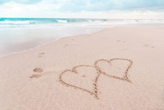 Hearts and Footprints on the Beach Stock Photos