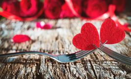 Hearts on forks in front of red roses. Concept Valentine`s Day dinner Stock Images