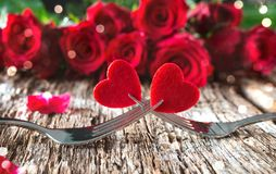 Hearts on forks in front of red roses. Concept Valentine`s Day dinner Royalty Free Stock Photos