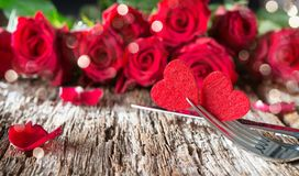 Hearts on forks in front of red roses. Concept Valentine`s Day dinner Royalty Free Stock Image