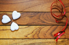 Hearts forming a clover and red ribbon. Hearts forming a clover with wood background and red ribbon Royalty Free Stock Photo