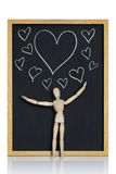 Hearts galore. Manikin, anatomical model, placed on a chalkboard with hearts drawn on it Royalty Free Stock Photos