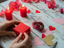 Hearts, gift, ribbons on wooden background. Woman`s hands making handmade valentines day decoration Stock Photography