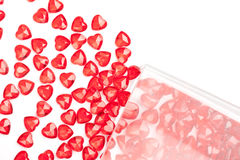 Hearts and Glass. Some red plastic hearts scattered out of a clear glass vase onto a white background Stock Photography