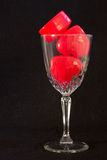 Hearts and glass. Three red dimensional hearts in cut-glass wine glass, isolated on black Royalty Free Stock Images