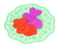 Hearts on a green paper lace doily Stock Photos