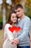 Hearts in the hands of a guy and a girl in focus against a backg Stock Photography