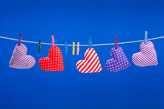 Hearts hanging on a clothesline with clothespins, blue backgroun Stock Images