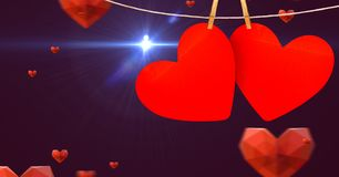 Hearts hanging on line against digitally generated background stock photo