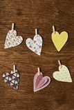 Hearts hanging in some clothes lines. Some nice hearts cut out from papers with different patterns hung with clothespins in some clothes lines, against a rustic stock photo