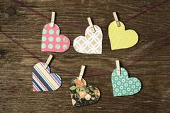 Hearts hanging in some clothes lines. Some nice hearts cut out from papers with different patterns hung with clothespins in some clothes lines, against a rustic stock photos