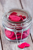 Hearts in jar. Red hearts in a closed and locked transparent jar on old wooden table. Selective focus Stock Image
