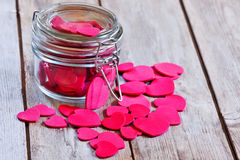 Hearts in jar. Red hearts in a closed and locked transparent jar on old wooden table. Selective focus Royalty Free Stock Photos