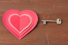 Hearts and key on wooden. Background Royalty Free Stock Photo