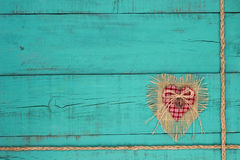 Hearts and lock with rope border on teal blue wood background. Shabby burlap, country fabric heart with lock and braided rope border on rustic antique teal blue stock photo