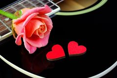 Hearts of lovers, beautiful rose and black acoustic guitar. Valentine& x27;s Day royalty free stock photos