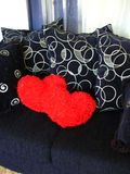 Hearts on Loveseat. Shot of a couple red hearts on a dark blue loveseat royalty free stock image