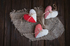 Hearts made of cloth. With red white checkered pattern on rustic old wood with copy space, concept of love at Christmas, Mother's Day or Valentine's Day Royalty Free Stock Photo