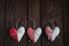 Hearts made of cloth. With red white checkered pattern on rustic old wood with copy space, concept of love at Christmas, Mother's Day or Valentine's Day Stock Photos
