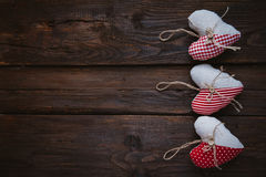 Hearts made of cloth. With red white checkered pattern on rustic old wood with copy space, concept of love at Christmas, Mother's Day or Valentine's Day Stock Images