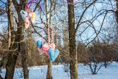 Hearts made of cloth in the wind. Hearts of fabric in the wind on a branch in forest in winter Royalty Free Stock Photography