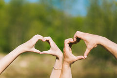 Hearts made by young couples hands Royalty Free Stock Images