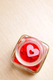 Hearts in open glass jar on wooden surface Royalty Free Stock Photos
