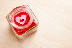 Hearts in open glass jar on wooden surface - Series 2 Stock Photos