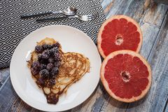 Hearts pancakes with blackberries on a white plate. blue wooden Background with grapefruit. Romantic or healthy stock photos