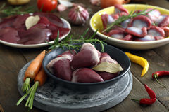 Hearts on plate. Fresh raw hearts on plate with other organs and fruits and vegetables on the background Stock Photos