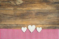 Hearts with red checkered fabric on brown wood. Stock Images