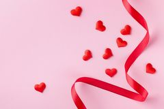 Hearts and red ribbon on pink pastel background for Valentines day card. Flat lay style stock photography