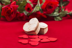 Hearts on red with roses in the background Royalty Free Stock Photos