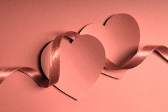 Hearts and ribbon. Couple of hearts and satin ribbon, monochrome image stock image
