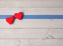 Hearts and Ribbon on White Wood Background. Two red fabric hearts and blue check gingham ribbon on white wood background with copy space for text Royalty Free Stock Photos
