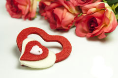 Hearts and roses. Red roses and hearts of red and white felt Stock Photos