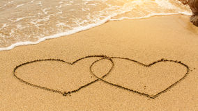 Hearts in the sand drawn by hand in the surf. Love. Stock Photography