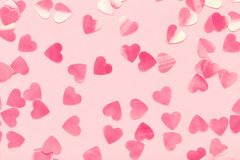 Hearts shape Confetti on pink pastel holiday background. Heart shape confetti on pink pastel holiday background. Festive abstract backdrop, Valentine`s Day, Love royalty free stock images