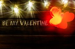 """Hearts shaped string lights on wooden table backdrop, with """"Be my Valentine"""" stock photo"""