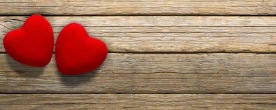 Valentine`s Day banner, red velvet hearts on old wooden floor. Hearts Shaped , Valentine`s day background stock images