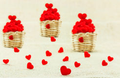 Hearts in small wooden weave basket putting on the sack fabric. Royalty Free Stock Image